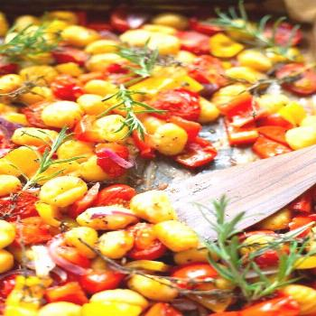 A tin gnocchi with tomatoes, peppers and red onions - a carousel -  Advertising. A tin gnocchi with