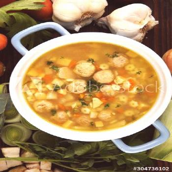 Broth with marrow dumplings and carrots, onions various fresh vegetables in a pot - colorful fresh