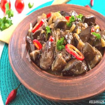 Pieces of fried turkey liver with onions in a clay bowl on a white wooden background. Diet menu. ,