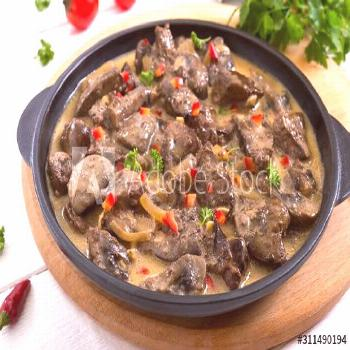 Turkey liver with onions and mushrooms in a creamy sauce on a white wooden background. Diet menu ,